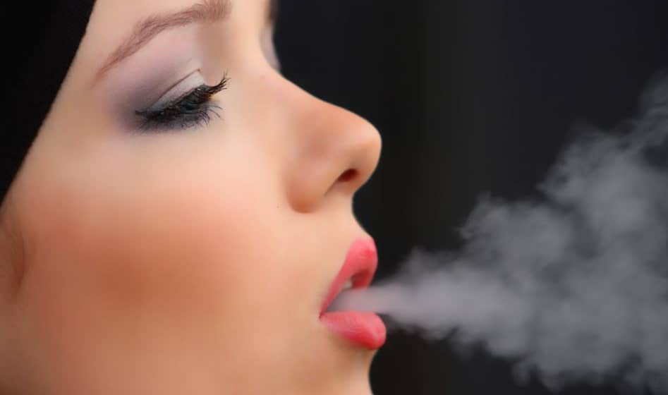 woman exhaling smokees
